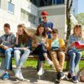 grupa uczniów na ławce przed szkołą