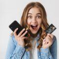 Młoda dziewczyna trzymająca kartę płatniczą i telefon