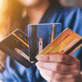 młoda osoba trzyma kilka różnych kart płatniczych