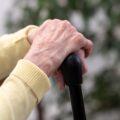 Dłonie staruszki oparte o laskę
