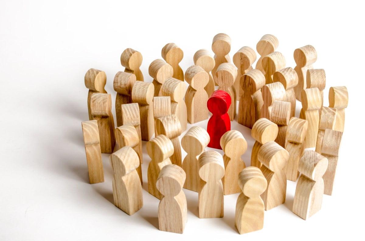 Grupa jednakowych figurek wokół jednej odróżniającej się od nich