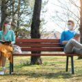 Para siedząca na ławce zachowująca dystans 1,5 m