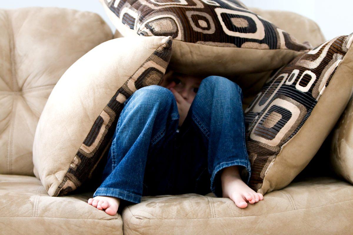 Chłopiec ukryty wśród poduszek