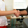 dwoje osób wita się uściskiem dłoni
