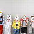 Kilka osób stoi z maskami - emotikonkami wyrażającymi emocje