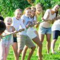 grupa młodzieży bawi się na pikniku w przeciąganie liny