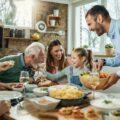 Rodzina składająca się z dziadków, rodziców i dzieci siedzi przy stole i śmieje się podczas jedzenia