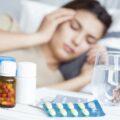 młoda kobieta leży chora na łóżku, a obok niej stoją lekarstwa