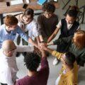 grupa osób z dłońmi jedna na drugiej. Symbol współpracy i akceptacji