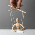 Dłoń manipuluje marionetką