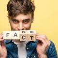 Młody człowiek trzyma w dłoniach klicki z napisem Fake/Fact