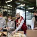 grupa młodych wolontariuszy pakuje paczki