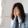 Smutna dziewczyna z twarzą ukrytą w dłoniach