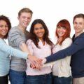 Grupa młodych ludzi w uścisku współpracy, przyjaźni