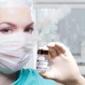 Kobieta, lekarka trzymająca fiolkę ze szczepionką przeciw Covid-19