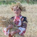 Dziewczyna w stroju ludowym stojąca na polu ze snopkiem w dłoni